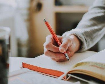 person-holding-orange-pen-1925536-min
